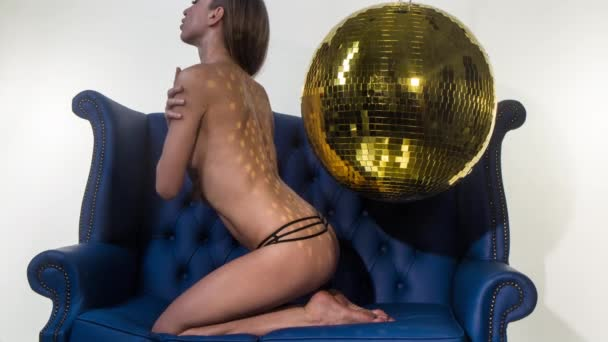Beautiful sexy topless woman posing on blue chair with disco ball