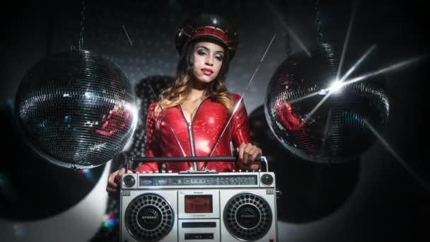 sexy coole Frau posiert in erstaunlichen roten Catsuit mit stacheligen Militärhut und Vintage Ghetto-Blaster