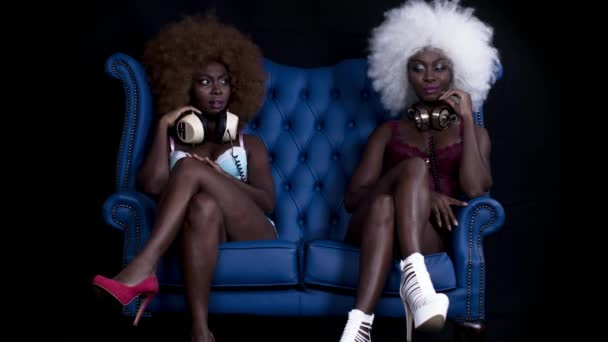 Absztrakt kompozit felvételeket gyönyörű afrikai női modell különböző afro-paróka pózol a kék bőr szék és kölcsönhatásban áll magával.