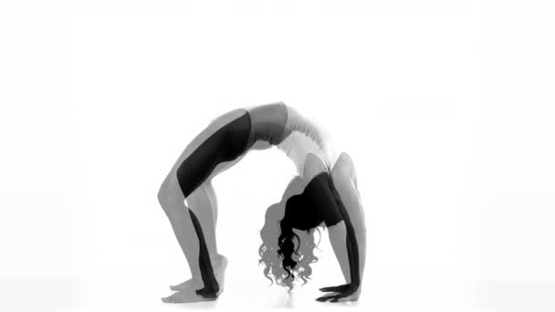Female yoga instructor moving against white background