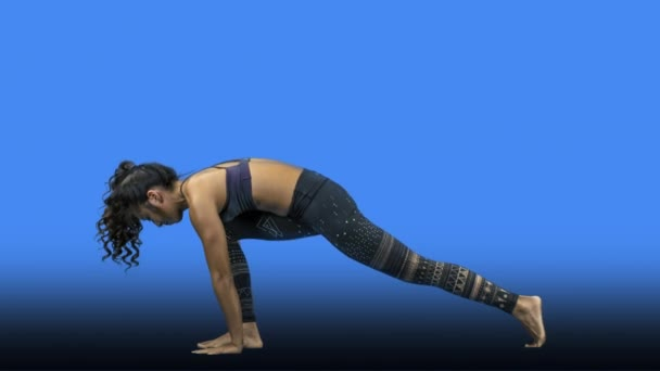 Young woman doing yoga on blue background