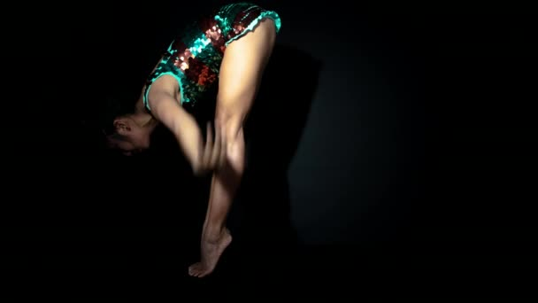Young woman in shiny costume doing exercises on black background