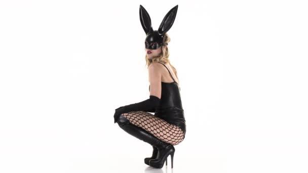 sexy Frau bewegt sich in Hasenohren Maske und schwarzem Latex-Körper