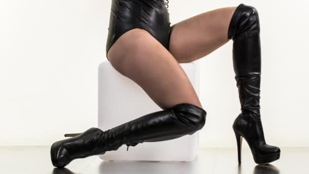 Beine einer sexy Frau posieren und tanzen in kniehohen schwarzen High Heels