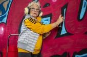 cool rebel grandmother painting graffiti against an urban wall