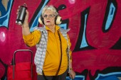 awesome rebel grandma graffiti artist against an urban wall