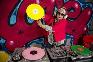 stylish grandma playing music on vinyl in front of graffiti wall