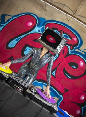 Tv head woman djing in front of the word love graffiti painted on a wall