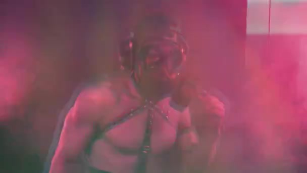Muscular man dancing in gas mask
