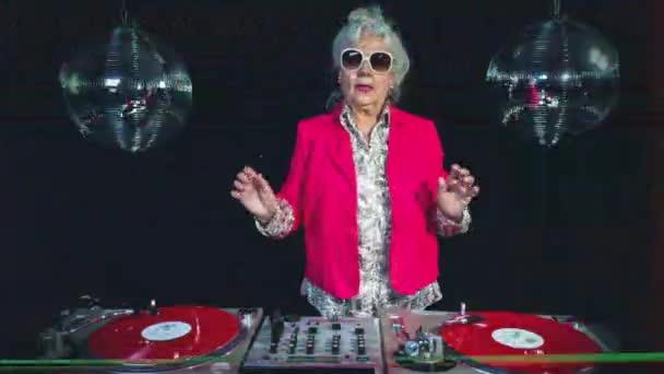 Senior woman in sunglasses djing against disco balls