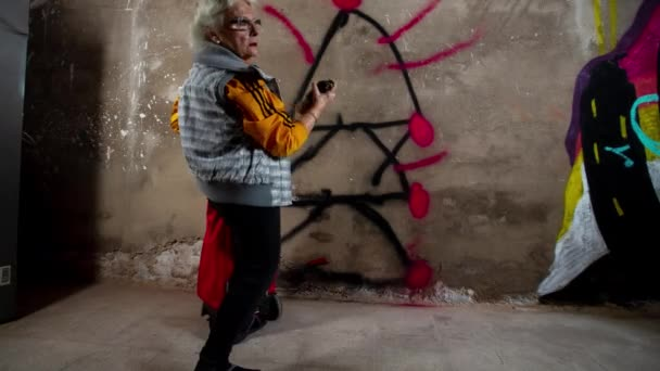 Senior woman with cart drawing graffiti on wall