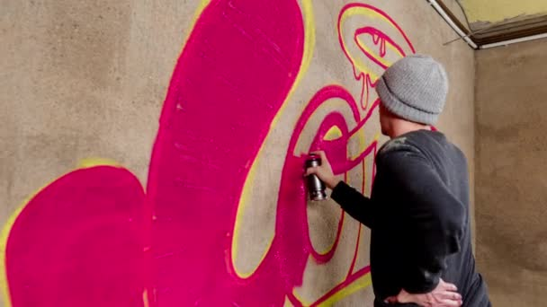 Process of graffiti artist spraying word love on concrete wall