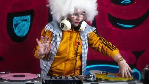 Starší žena v DJingu sluchátka proti graffiti