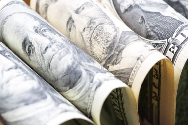 blurred dollars banknote rolled up and close up concept of economy