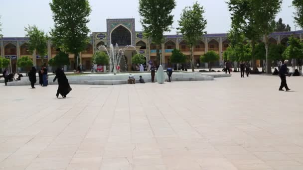 people walking on old square of minaret in iran