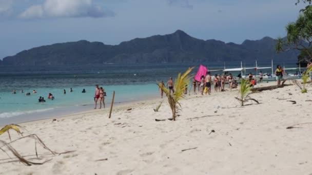 CORON, PHILIPPINES - CIRCA DECEMBER 2016 - unidentified people on beautiful beach near boats