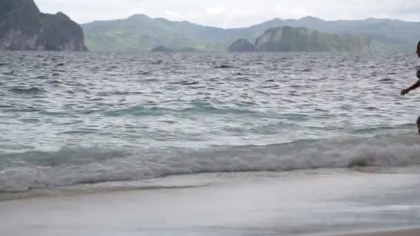 people relaxing on sandy beach near rock hills in philippines waves of pacific ocean, concept of relax