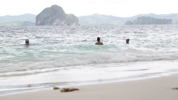 people from a boat and hill in philippines waves of pacific ocean near the sandy beach, concept of relax