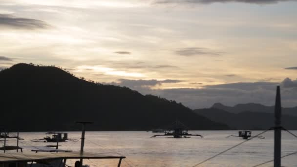 boats with people on water at evening, mountains on background