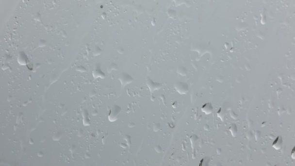 Detailní záběry vodních kapek na okenní sklo s rozmazané pozadí