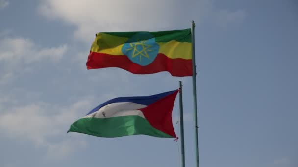 bottom view of waving Ethiopian Flag and Flag of Afar against cloudy sky