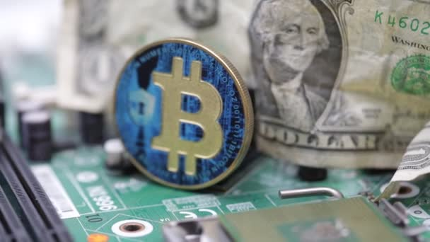 Close-up footage of coin with bitcoin sign and crumpled dollar banknote on  computer circuit