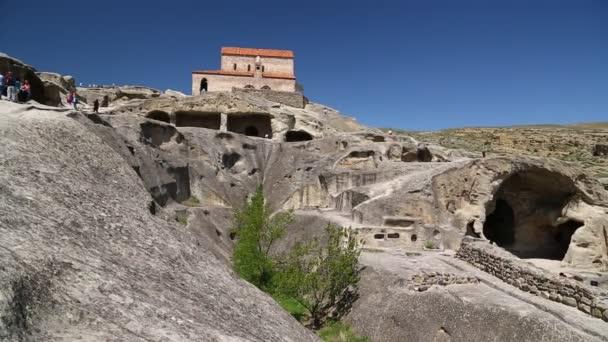 lidé chodící ve starověkém městě s rockem uplistsikhe ve východní Gruzii