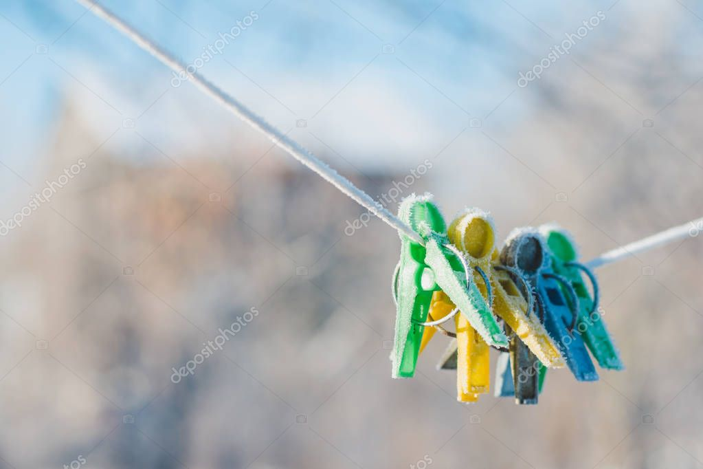 Green, yellow and blue clothespins on a rope, covered with winter hoarfrost