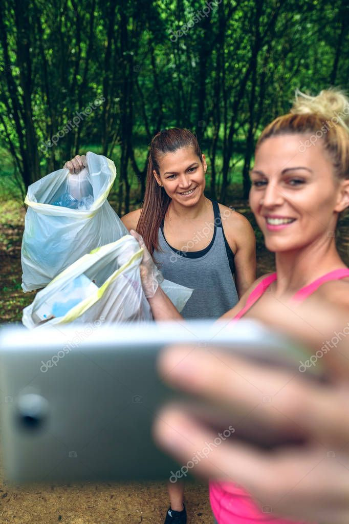 Two happy girls taking a selfie showing trash bags after plogging. Selective focus on girl in background