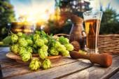 Čerstvé studené pivo v rustikálním prostředí s čerstvým chmelem
