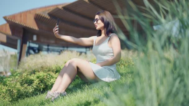 Young woman making selfie sitting on green grass