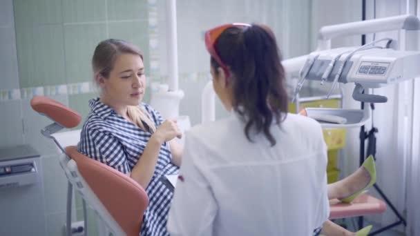 Zahnärztin in Zahnarztpraxis erklärt einer Patientin ihre Arbeit