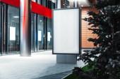Stojan prázdný osvětlený nápis vedle moderní budovy v noci, vykreslování 3d objektů.