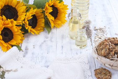Sunflower oil and large yellow flowers. Oil in the bottle. Without peel of sunflower seeds and cookies. White wooden background. Vintage photo. Organic food. Copy space. Flat lay