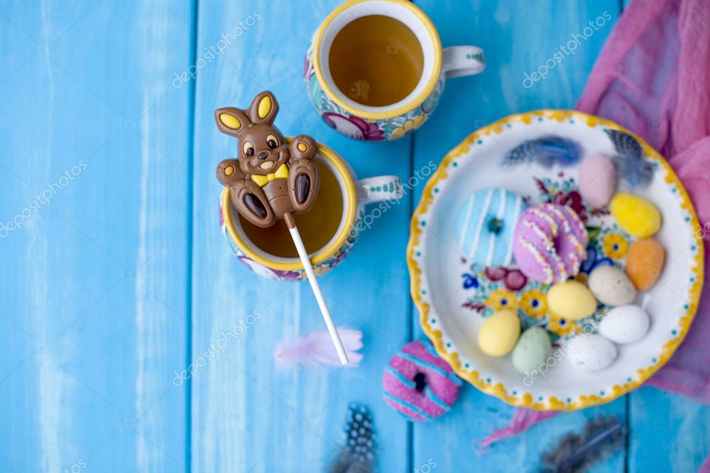 Easter sweets for the holiday. Spring. Bright colors on coffee mugs. Chocolate bunny. View from above.