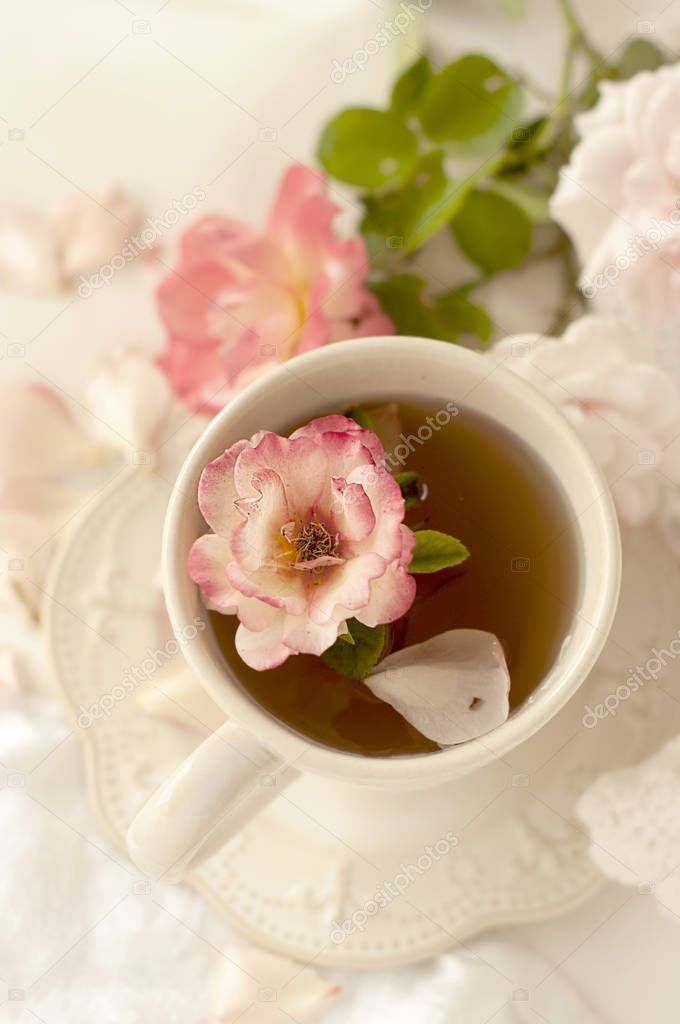 Aromatic tea in a vintage mug and pink roses, a delicious and beautiful breakfast. Pastel shades