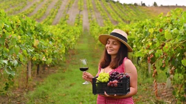 Žena v klobouku se sklenicí vína a krabicí hroznů. Žena na farmě v období sklizně.