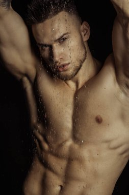 Handsome sport sexy stripped guy portrait in water drops on isolated black background