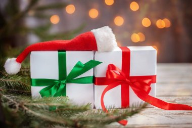 Christmas white boxes or presentes with santa hat on white wooden table