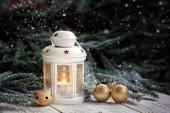 Zimní vánoční výzdoba v teplém světle lucerny, zlatá vločka a koule, větve jedle a ornamenty na tmavém pozadí