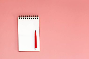Workspace with Blank spiral notebook with red pen on Coral Background. Top view