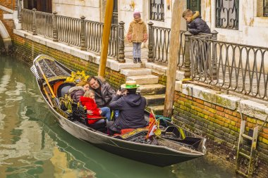 VENICE, ITALY, JANUARY - 2018 - Family being photographed by gongolier at venice channel, Italy