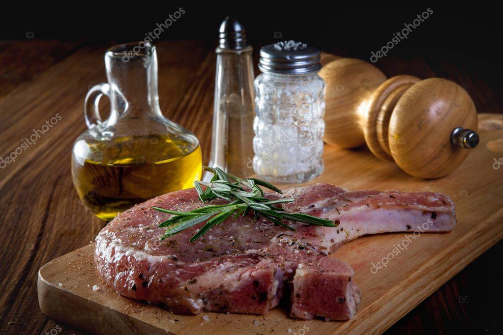raw pork chop steak on wooden background.