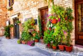 Bájos régi középkori falvak Olaszország tipikus virágos keskeny utcáin. Spello, Umbria állam