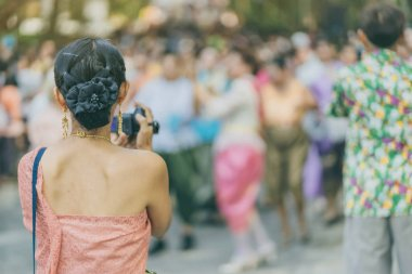 Back view of female in Thai dress  take a photo of a Thai dance parade in Songkran festival