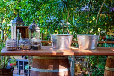 Wine Buckets And Candle holders On A Bar In A Garden