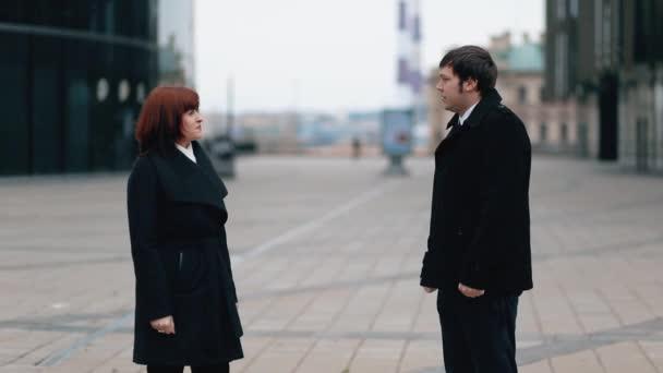 Mužský obchodník a obchodnice v černém plášti se dohodnou na dohodě a potřesou si spolu rukou..