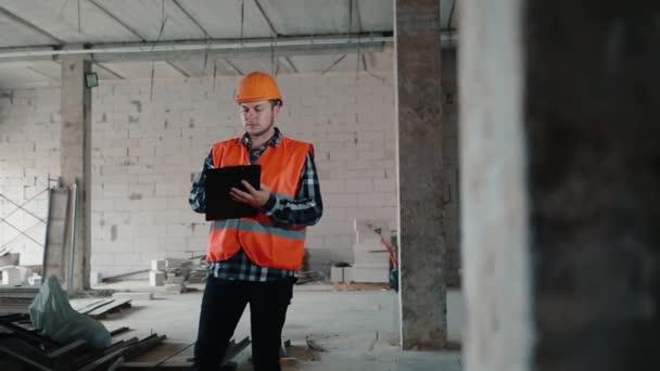 Pracovník ve stavebnictví stojí v místnosti a zapisuje data do složky tabletu..