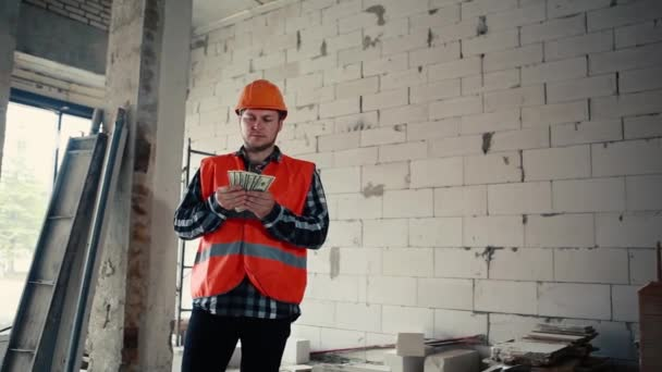 A male builder stands in a building amid a construction site and slowly recounts the money, then puts it in his pocket.