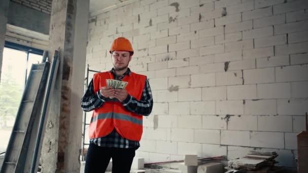 Muž stavitel stojí v budově uprostřed staveniště a pomalu přepočítává peníze, pak je strčí do kapsy.